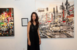 """artist Brooke Harker in front of her painting """"Grauman's Chinese Theatre"""""""