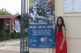artist Brooke Harker with exhibition banner in Italy