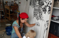 Brooke Harker paints with a toddler assistant